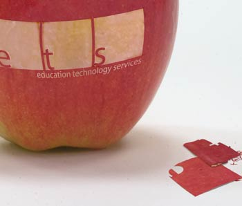 Apple with e t s cut into it.